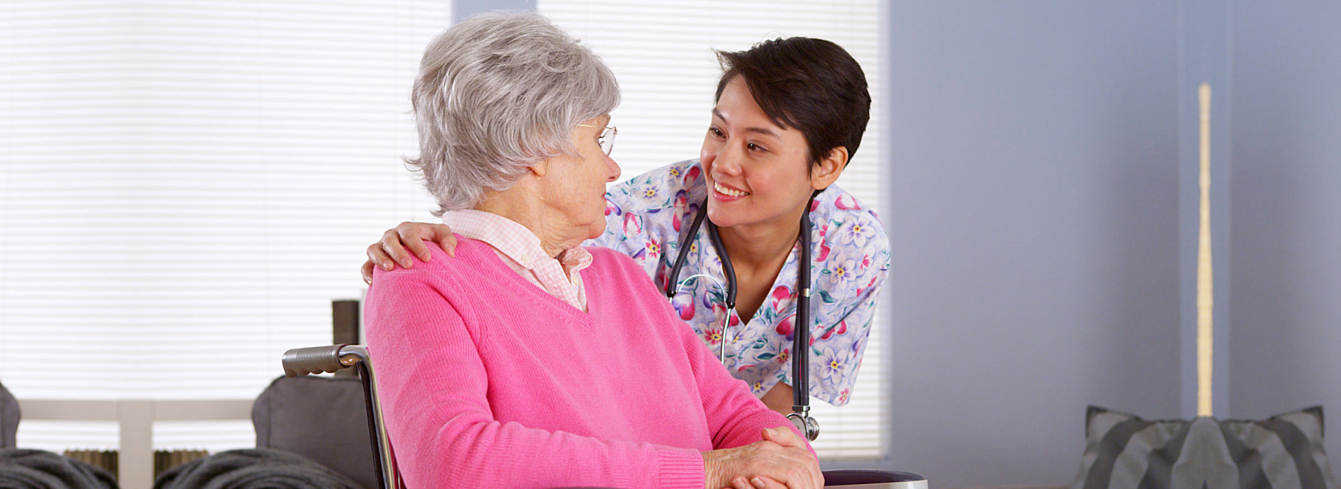 caregiver talking to an elderly woman