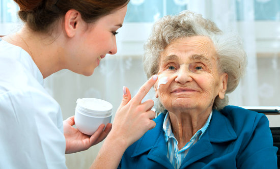 caregiver putting a cream on elderly woman's face